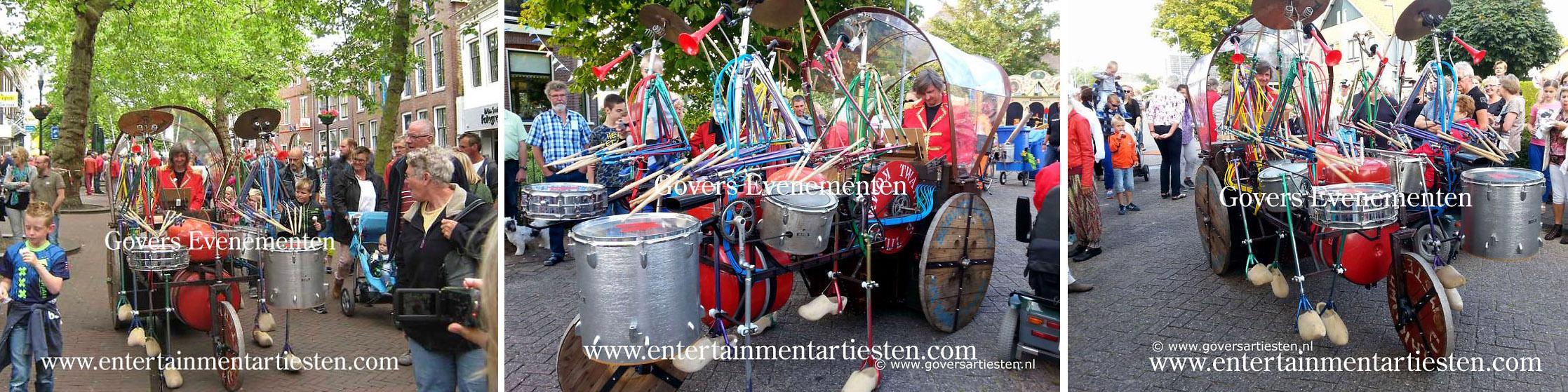 Straatact, muziek, bandje, straatmuziek, Straattheater, Het rollende object Uit het land waar roest nooit rust en afval niet bestaat komt klompengeklos, een drumband met houten klompen als loopmachine, www.goversartiesten.nl